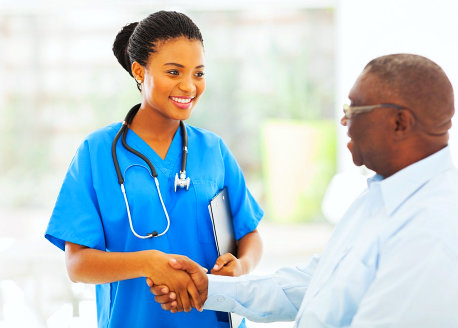 a caregiver woman smiling while shaking hands with a man